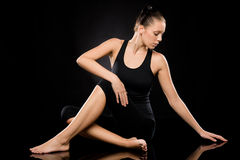 Attractive young woman in spine twisting pose Royalty Free Stock Image