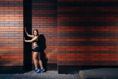 An attractive young woman in sportswear posing against a brick wall background with copyspace. Training outdoors stock photography