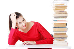 Attractive young woman with stack of books. Royalty Free Stock Photos