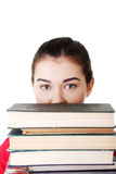 Attractive young woman with stack of books. Royalty Free Stock Photography