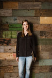 Attractive young woman standing against a wooden wall in office Royalty Free Stock Images