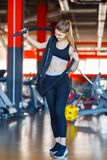 An attractive young woman standing in a fitness center posing with a physical rope over her shoulder. Royalty Free Stock Photography