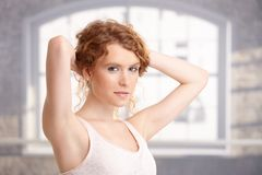 Attractive young woman standing front of window Stock Images