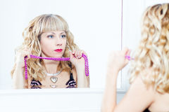 Attractive young woman standing next to the mirror Stock Image