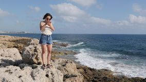 Attractive young woman standing on rock at seashore and looking to the phone. Caucasian brunette girl standing near sea with phone. In hands stock video footage