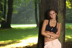 Attractive young woman standing by the tree Stock Photo