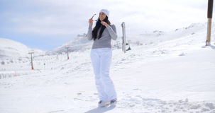 Attractive young woman standing in winter snow. At a mountain ski resort standing on a slope looking out over the scenery with her sunglasses in her hand  with Stock Photos