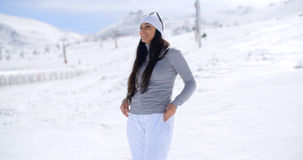Attractive young woman standing in winter snow. At a mountain ski resort standing on a slope looking out over the scenery with her sunglasses in her hand  with Royalty Free Stock Photography