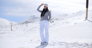Attractive young woman standing in winter snow. At a mountain ski resort standing on a slope looking out over the scenery with her sunglasses in her hand  with Royalty Free Stock Images