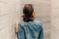 Attractive young woman stands between concrete walls. Caucasian girl in casual jeans looks up. Royalty Free Stock Photo