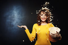Attractive young woman staying under popcorn shower with hand up. Attractive young woman staying under popcorn shower with right hand up. Isolated on black Stock Photography