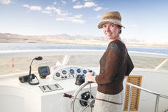 Attractive young woman steering a boat Stock Photo