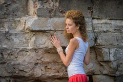 Attractive young woman and stone wall Royalty Free Stock Photo