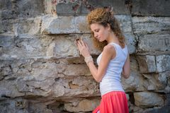 Attractive young woman and stone wall Stock Photos