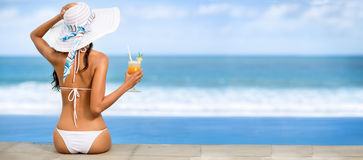 Attractive young woman in straw hat. Enjoy in sunny summer day with cocktail Royalty Free Stock Photos