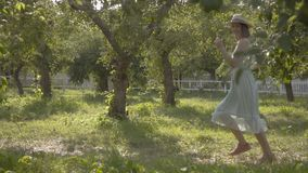 Attractive young woman in straw hat and long white dress running through the green summer garden. Carefree rural life. Attractive young woman in a straw hat and stock video footage