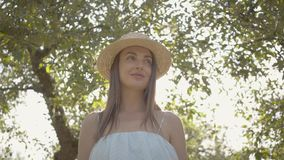Attractive young woman in straw hat and long white dress standing in the green summer garden. Sun shining behind the. Girl. Rural lifestyle stock video footage