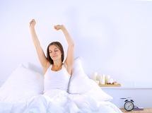 An attractive young woman stretching in bed after waking up Stock Image