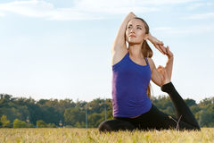 Attractive young woman stretching in the park. Attractive young woman in workout gear stretching Stock Photos