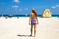 Attractive young woman in stylish mini dress walking towards Atlantic ocean at Miami beach, Florida, with rescue lifeguard tower stock images