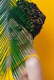 An attractive young woman in a stylish turban made of leopard print fabric on a yellow mango background. Girl with bright makeup. Beach style, palm branch