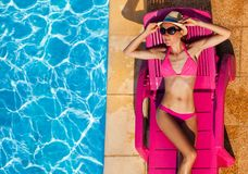 Attractive young woman sunbathing on chaise lounge Royalty Free Stock Photos