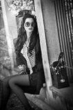 Attractive young woman with sunglasses in autumnal fashion shot. Beautiful lady in black and white outfit with short skirt sitting Stock Photo