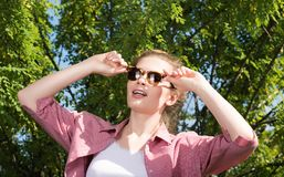Attractive young woman in sunglasses posing in nature and clings to glasses hands Royalty Free Stock Photos