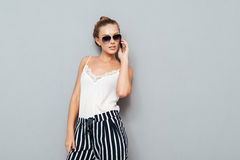Attractive young woman in sunglasses talking on mobile phone Stock Photos