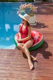 attractive young woman in swimsuit sitting on inflatable ring royalty free stock images