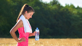 Attractive young woman taking a break after jogging, holding bottle of water Stock Photos