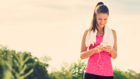 Attractive young woman taking a break after jogging, holding smartphone Stock Image
