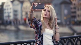 Attractive young woman is taking selfie on the black bridge cross the water canal, charming smile and sexy look. The stock footage