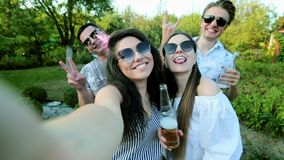 Attractive young woman is taking selfie with friends on birthday party, girl is holding camera, people gesticulate and stock video