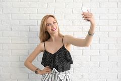 Attractive young woman taking selfie near brick wall Stock Photography