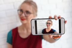 Attractive young woman taking selfie near brick wall Royalty Free Stock Photo
