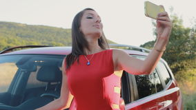 Attractive young woman taking selfie on the phone near her car stock video footage