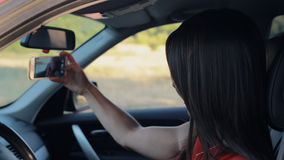Attractive young woman taking selfie on the phone while sitting in her car stock footage