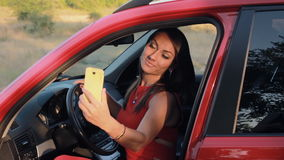 Attractive young woman taking selfie on the phone while sitting in her car. HD stock video footage