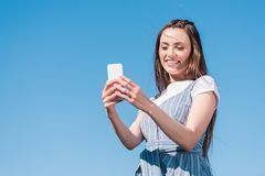 attractive young woman taking selfie on smartphone against blue royalty free stock images