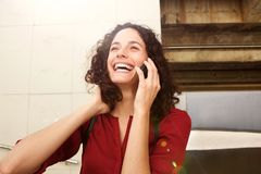 Attractive young woman talking on cell phone on laughing Stock Photo