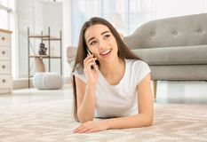 Attractive young woman talking on mobile phone. At home Stock Photos