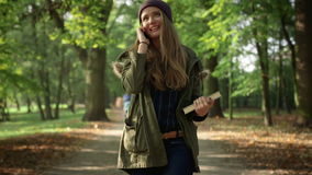 Attractive young woman talking on mobile phone in beautiful autumn park. stock video