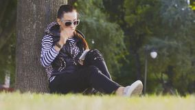 Attractive young woman with talking on mobile phone in beautiful autumn park. stock footage