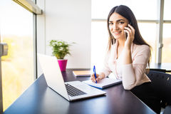 Attractive young woman talking on the mobile phone and smiling while sitting at her working place in office and looking at camera Stock Photography