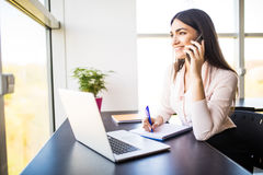 Attractive young woman talking on the mobile phone and smiling while sitting at her working place in office and looking at window Stock Photography