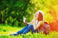 Attractive young woman talking by phone and holding cup of coffee Royalty Free Stock Image