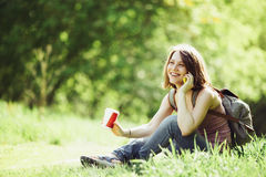 Attractive young woman talking by phone and holding cup of coffee Royalty Free Stock Images