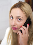 Attractive young woman talking on phone stock image