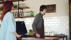 Attractive young woman is talking to friendly male cashier, paying for takeaway coffee with mobile phone at coffee shop